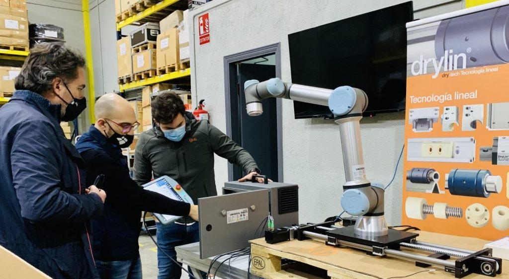 Equipo técnico de igus mostrando el 7º eje para el cobot de Universal Robots